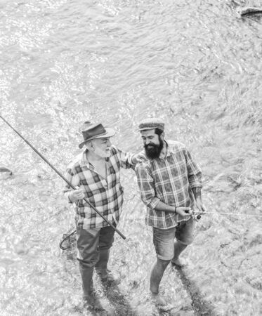 Weekends made for fishing. Active sunny day. Fishermen fishing equipment. Hobby sport activity. Fishermen friends stand in river. Fish normally caught in wild. Summer leisure. Men bearded fishermen