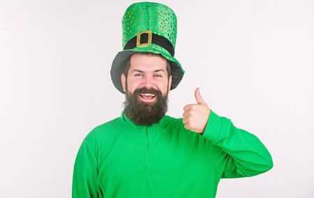 Showing his thumbs up. Happy irish man with beard wearing green. Hipster in leprechaun hat and costume. Bearded man celebrating saint patricks day. Happy saint patricks day