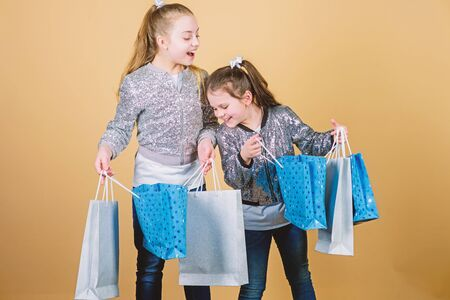 Sale and discount. Shopping day. Children hold bunch packages. Kids fashion. Expect more. Pay less. Girls sisters friends with shopping bags beige background. Shopping and purchase. Black friday
