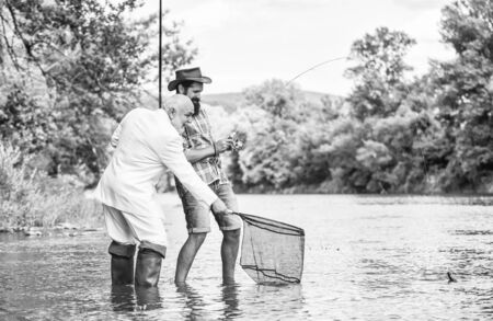 successful catch. hobby of businessman. retirement fishery. friends men with fishing rod and net. Fly fishing adventures. happy fishermen. Good profit. retired dad and mature bearded son