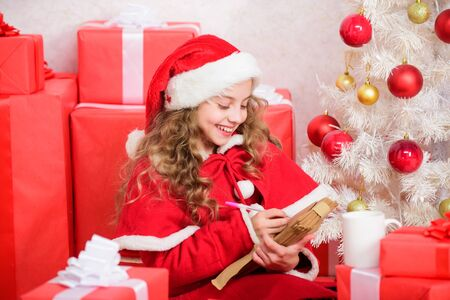 Girl little kid hold pen and paper near christmas tree writing letter. Child write letter to santa claus. Child santa costume enjoy christmas eve. Believe in miracle. Letter for santa. Wish list