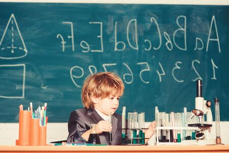 Basic knowledge primary school education. Educational experiment. Happy childhood. Boy near microscope and test tubes school classroom. Knowledge concept. Knowledge day. Kid study biology chemistry