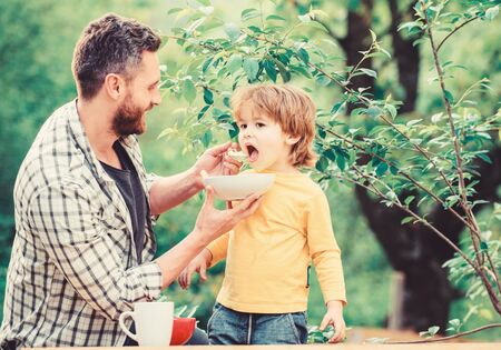 Nutrition habits. Little boy and dad eating. Nutrition for kids and adults. Healthy nutrition concept. Feeding baby. Menu for children. Family enjoy homemade meal. Father son eat food and have fun