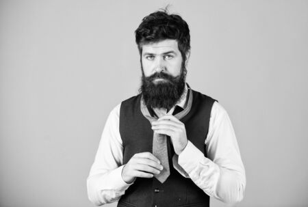 Art of manliness. How to tie necktie. Start with your collar up and the tie around your neck. How to tie simple knot. Man bearded hipster try to make knot. Different ways of tying necktie knots