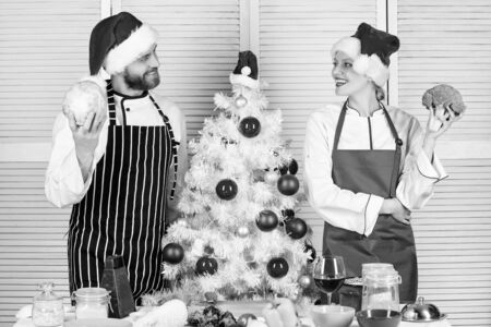 Christmas recipe concept. Secret ingredient is love. Couple preparing healthy meal together for christmas dinner. Cooking christmas meal. Man and woman chef apron santa hat near christmas tree