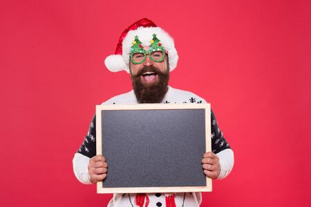 Ski rental concept. Winter price drop. Bearded hipster Santa claus. Joyful man show blackboard copy space. Happy winter holidays. Presentation or announcement. Promoting winter goods and services. 版權商用圖片