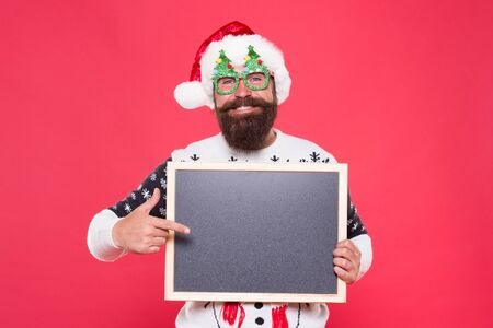 Presentation announcement. Promoting winter goods. Profitable offer here. Rental services. Winter price drop. Bearded hipster Santa claus. Joyful man show blackboard copy space. Happy winter holidays. Banque d'images