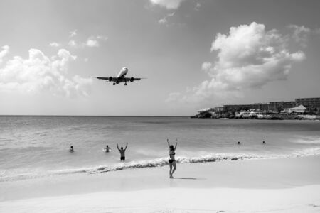 Plane land over people on beach of philipsburg, sint maarten. Jet flight low fly over blue sea. Airplane in cloudy blue sky. Beach vacation at Caribbean. Wanderlust, travel and trip. Stock Photo