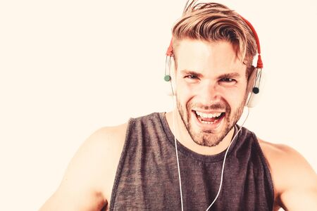 man wearing headphones playing music. unshaven man listening music in headset. sexy muscular man listen sport music. man in earphones isolated on white