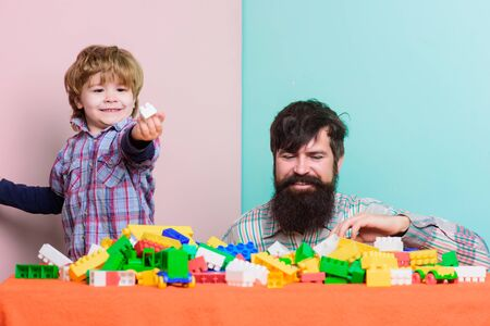 Bearded father and boy play together. Father son play game. Dad and kid build of plastic blocks. Father and son create colorful constructions with bricks. Child care development and upbringing