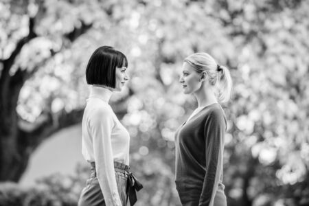 two women are facing each other. girls looking into each others eyes. female friendship. walking in sunny park. best friends. chance meeting. Friendship is over. Portrait of two beautiful women.