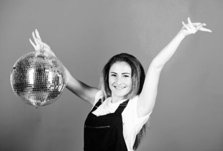 Night club. Retro music. Girl inviting at party. Mirrors reflecting lights disco atmosphere. How about party. Little party never killed nobody. Dance until drop. Cheerful woman hold disco ball