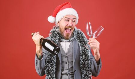 Corporate christmas party. Lets drink champagne. Boss santa hat tinsel celebrate new year or christmas. Join christmas celebration. Christmas party invitation. Man bearded hipster santa hold bottle Stock fotó