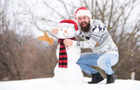 Winter games. Hipster with beard outdoors. Man with Santa hat having fun outdoors. Guy happy face snowy nature background. Winter activity. Fun and entertainment. Winter vacation. Man made snowman Stock fotó