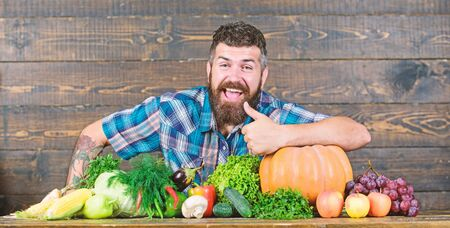 Welcome to my farm. Farmer with homegrown vegetables. Vegetables organic harvest. Farmer rustic style guy. Natural foods. Vegetarian lifestyle concept. Man bearded farmer harvest wooden background