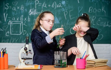 Basic knowledge of chemistry. Girls study chemistry. Make studying chemistry interesting. Educational experiment concept. Microscope and test tubes on table. Be careful performing chemical reaction Stock fotó