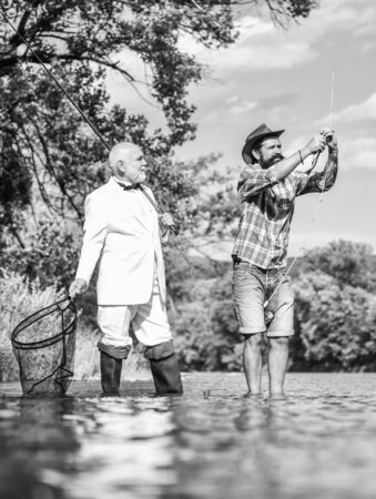 Perfect weekend. Successful catch. Elegant bearded man and brutal hipster fishing. Hobby and recreation. Family day. Summer vacation. Friends fishing. Fishing as holiday. Fisherman in formal suit
