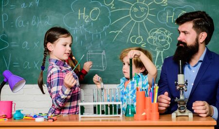 Interests and topic club. Older kids help younger. School club education. Teacher and pupils test tubes in classroom. Chemistry themed club. Discover and explore properties of substances together