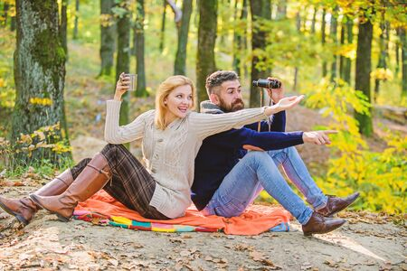 Look there. Relaxing in park together. Happy loving couple relaxing in park together. Couple in love tourists relaxing picnic blanket. Man with binoculars and woman with metal mug enjoy nature park Stock fotó