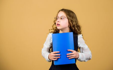 serious small girl wants to be teacher. small girl with paper folder. hometwork. notebook for diary notes. study lesson. knowledge and education. Back to school. Concentrated on studying. copy space