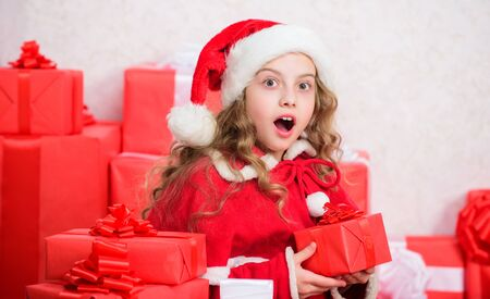 Girl celebrate christmas. Santa bring her gift. Winter happiness concept. Explore christmas gifts. Unpacking christmas gift. New year holiday tradition. Kid excited about opening christmas present Stock fotó
