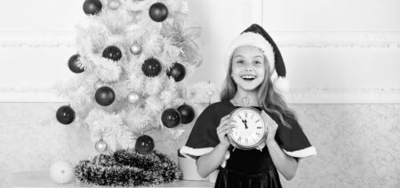 New year countdown. Girl kid santa hat costume with clock excited happy face counting time to new year. Last minute till midnight. Last minute new years eve plans that are actually lot of fun Stock fotó