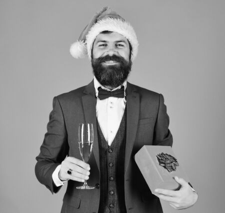 Manager with beard holds glass of champagne and gift.