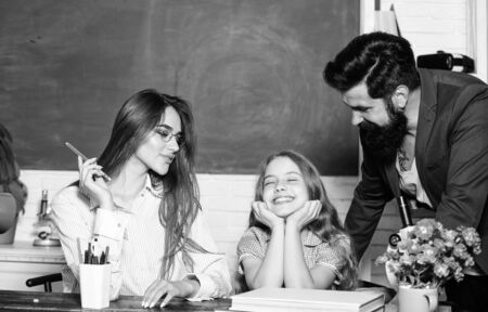 Teaching daughter. Favorable conditions for learning. Good learning environment. Learners must feel supported welcomed and respected. Mom and dad teachers helping child with learning. Smart family Stock fotó
