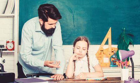 let me help you. bearded man teacher with small girl in classroom. daughter study with father. Teachers day. education child development. back to school. knowledge day. Home schooling