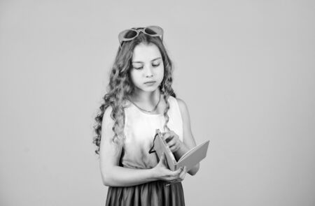 small happy girl in glasses with notebook. diary notes. reading book. Summer fashion. small beauty girl write her memories. making plans for summer holidays. school child with album for painting Stock fotó