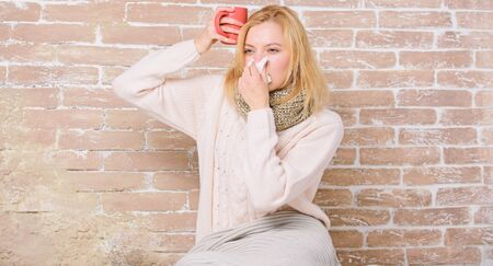 Drinking plenty fluid important for ensuring speedy recovery from cold. Cold and flu remedies. Drink more liquid get rid of cold. Girl hold tea mug and tissue. Runny nose and other symptoms of cold