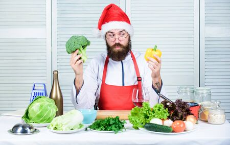 Christmas diet. Enjoy healthy christmas dinner. Healthy christmas holiday recipes. How make your christmas dinner healthier. Man bearded chef wear santa claus hat cooking. How to enjoy holiday meals Archivio Fotografico