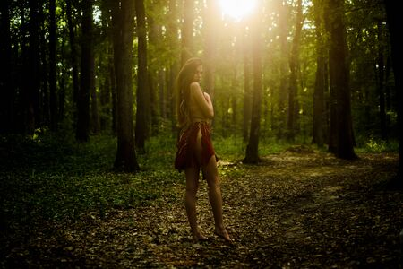 Dangerously sexy. amazon woman. sexy witch. cougar female. sexy girl in leather suede clothes. wild woman in forest. ethnic tribal fashion. deep forest. female silhouette through the sun rays Stock Photo