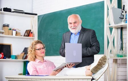 In the school. student girl with tutor man at blackboard. pass exam. teachers room. modern school education. student and tutor with laptop. senior teacher and woman at school lesson