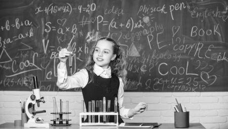 Futur microbiologiste. Laboratoire scolaire. Une étudiante intelligente mène une expérience scolaire. L'élève de l'école étudie les liquides chimiques. Leçon de chimie à l'école. Tubes à essai avec des substances. L'éducation formelle