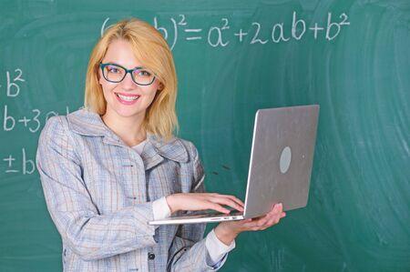 Woman teacher wear eyeglasses holds laptop surfing internet. Educator smart clever lady with modern laptop searching information chalkboard background. Learn it easy way. Digital technologies concept