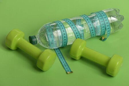 Sports regime equipment. Dumbbells in bright green color, water bottle and measure tape on green background. Healthy lifestyle and low calorie drink concept. Bottle wrapped with cyan ruler by barbells