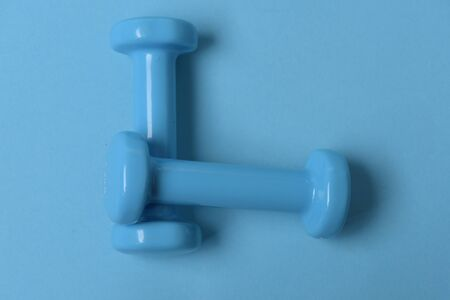 Fit shape and sport concept. Health regime and fitness symbols. Dumbbells made of blue plastic on cyan background. Barbells in small size, top view Stock Photo