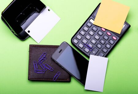 Stationery, wallet, phone and calculator. Business cards with copy space and clips with stickers. Wallet, mobile phone and hole punch on green background. Business accessories and gadgets concept. Foto de archivo - 135496563