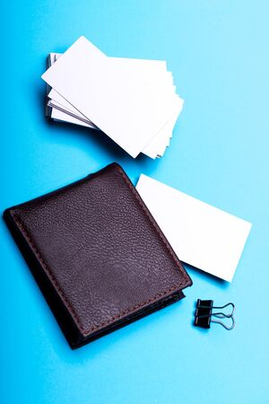 Business cards stack on cyan blue background. Business finance and contacts concept. Personal presentation accessory and leather wallet in close up. Name cards in white color with copy space. Foto de archivo - 135496692