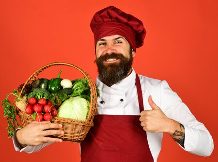 Cook with happy face in burgundy uniform holds vegetables