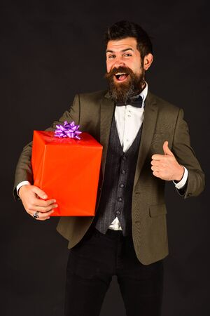 Macho in retro suit presents wrapped gift. Birthday present concept.