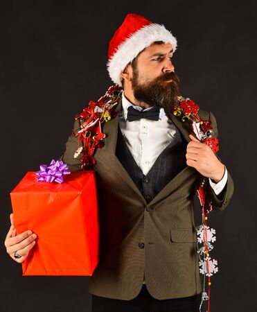 Manager with beard holds red gift. New Year decorations concept. Reklamní fotografie
