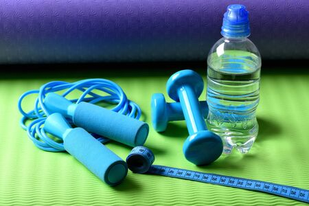 Workout and refreshment concept. Skipping rope, cyan dumbbells and tape near water bottle on green and purple background. Bottle or water near jump rope and barbells on yoga mat. Sports and health