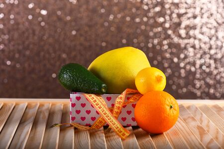 Fruits in box with hearts pattern on wooden surface. Lemon, orange, melon and avocado with yellow measuring tape on beige bokeh background. Composition of fruits. Healthy diet and slim shape concept