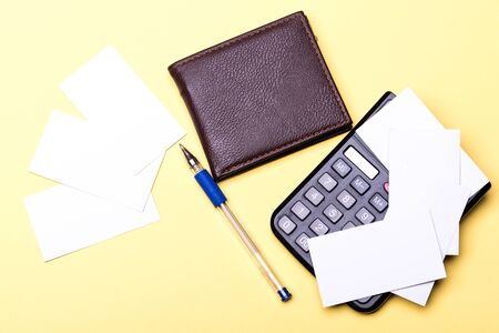 Leather wallet, calculator and cards with pen on yellow background. Stationery, money and calculator. Business cards with empty space and calculating. Office supplies and finance concept. Foto de archivo - 135496597