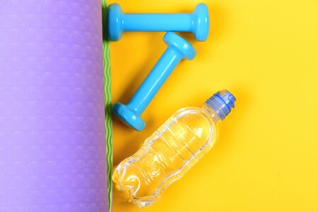 Dumbbells made of cyan plastic on yellow and purple background. Shaping and fitness equipment. Barbells and water bottle lying on yoga mat. Workout and sport concept