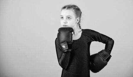 Contrary to stereotype. Boxer child in boxing gloves. Female boxer change attitudes within sport. Rise of women boxers. Girl cute boxer on blue background. With great power comes great responsibility Foto de archivo