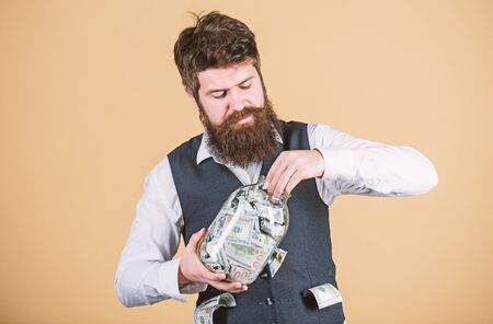 Making an investment. Businessman taking cash money out of glass jar for investing activities. Bearded man investing money into startup business. Investing for future benefit. Investing capitalist