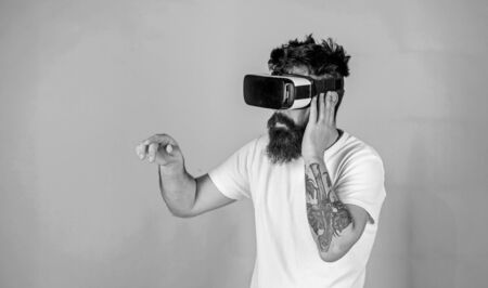 Man performing musical show in virtual reality simulation game. Bearded man with tattoo wearing VR headset. Man with hipster beard using digital touch screen interface, virtual reality concept. Banco de Imagens